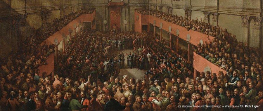 Obraz przedstawia wielu ludzi siedzących przy ławach w dużym pomieszczeniu. Jest to symboliczne przedstawienie dnia 3 maja, w którym uchwalono Konstytucję