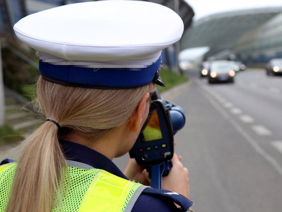policjantka ruchu drogowego kontroluje prędkość trzymając w ręku miernik prędkości - widok z tyłu