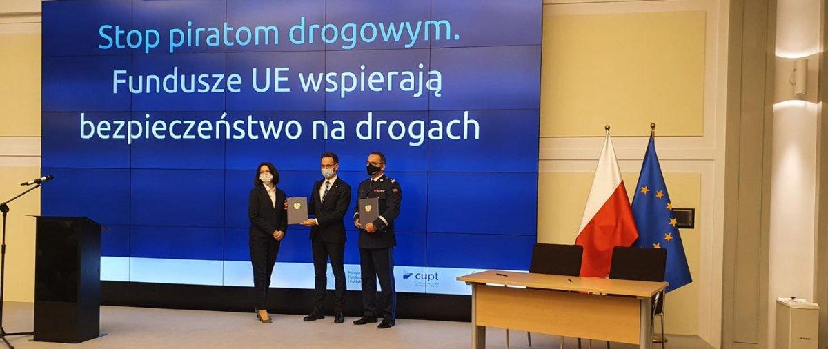 Na scenie stoją trzy osoby, które prezentują dokumenty. Od lewej Joanna Lech, Waldemar Buda i Dariusz Augustyniak. Za nimi na ekranie napis: Stop piratom drogowym. Fundusze UE wspierają bezpieczeństwo na drogach. Na scenie stoi mównica, mikrofon, stolik z krzesłami i dwie flagi PL i UE.