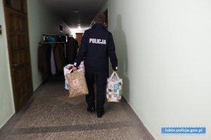 klatka bloku. policjanci niosą paczki z odzieżą