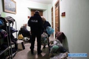 policjant przekazuje kobiecie paczki z ubraniami