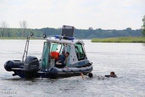 policyjna łódź na brzegu której kuca funkcjonariusz, podpływa do dwóch osób znajdujących się w wodzie