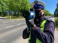 Umundurowany policjant w kamizelce odblaskowej stoi przy drodze i dokonuje pomiaru prędkości ręcznym miernikiem prędkości.
