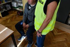 Podejrzany siedzi na krześle z rękami zakutymi w kajdanki, widoczna również policjantka